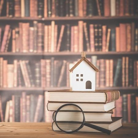 Magnifying glass on books with cut out house on top