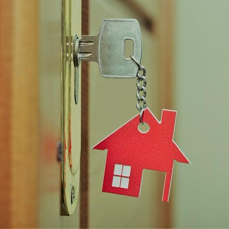 house key with red keyring in door